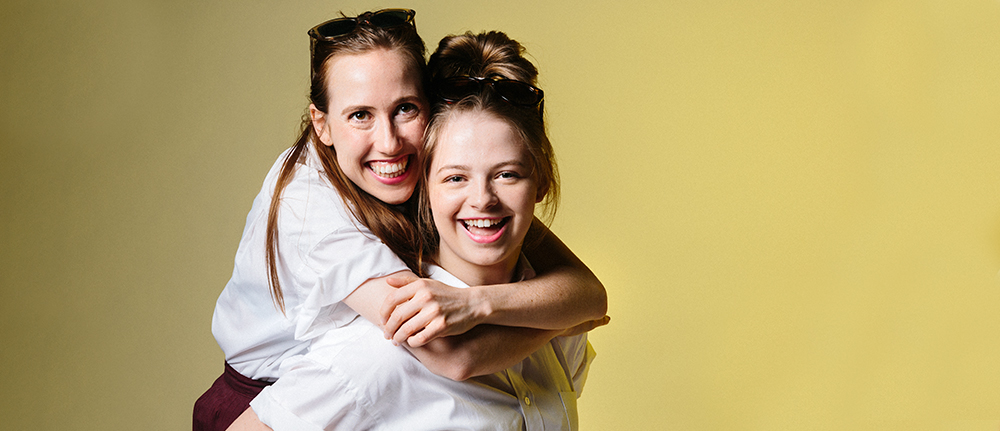 Two teenage girls in school uniform. One hugging the other from behind they both look into the camera smiling.