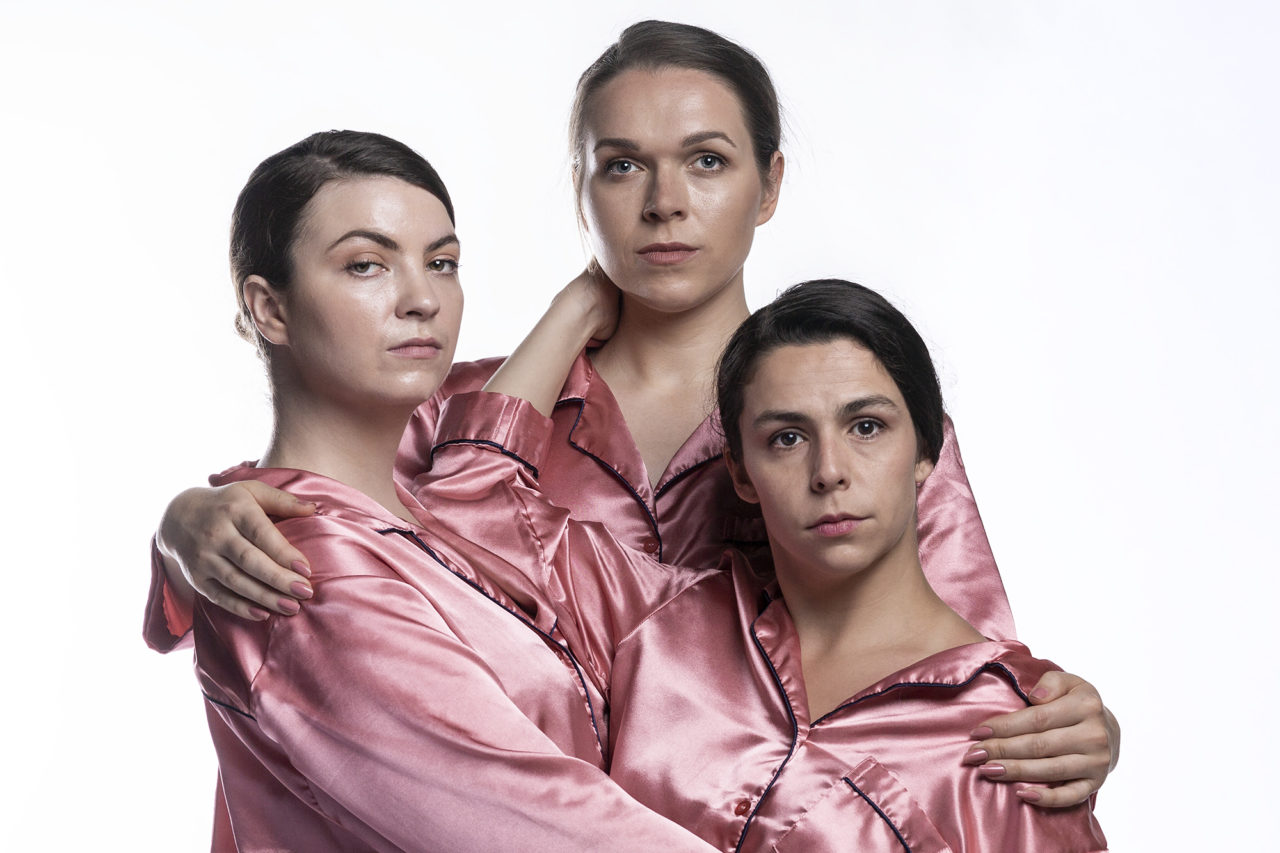 Three people in pink satin pyjamas holding each other and looking into the camera