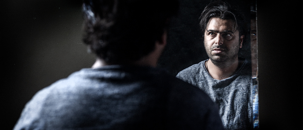 The back of a man's head you can see his face looking back into a mirror. He has dark hair and skin and has a distressed expression on his face.