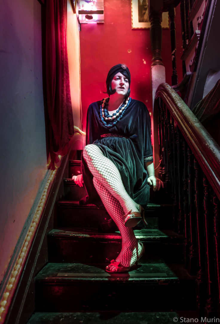 A cabaret artist sitting on stairs