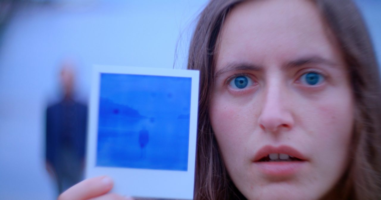 A person with fair skin and hair. They have piercing blue eyes and are holding a polaroid picture up to the camera.