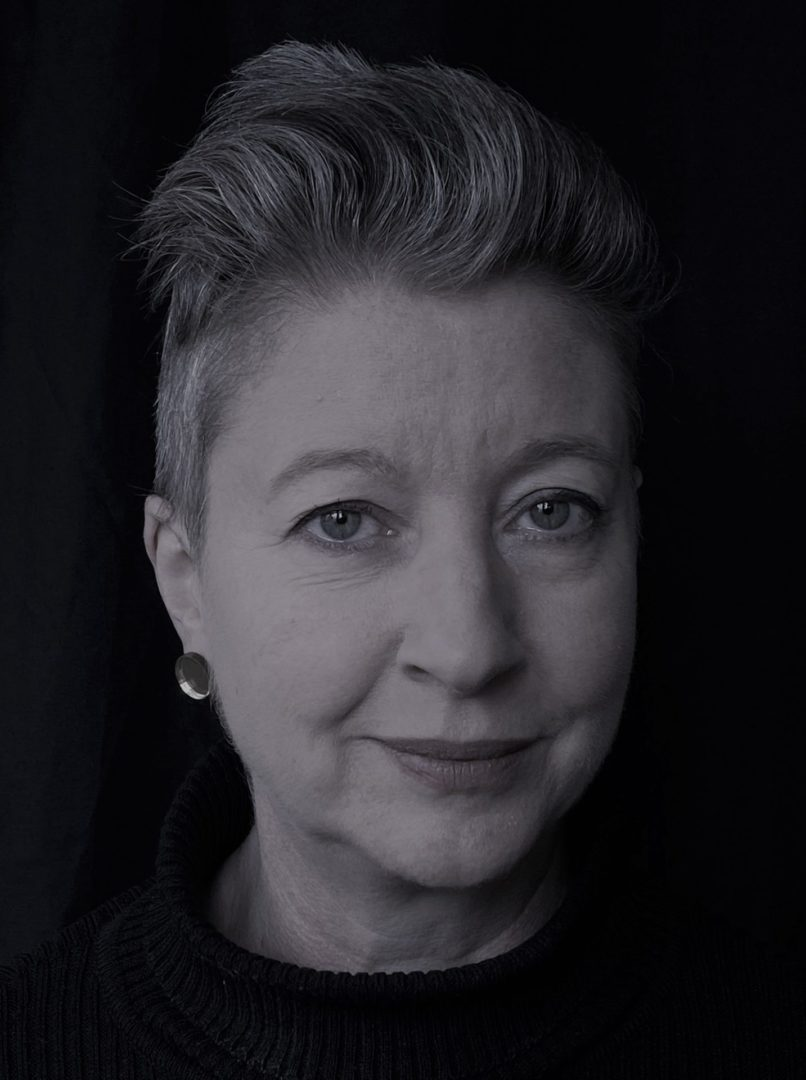 A black and white close up of a white woman with short cropped hair and earrings on.