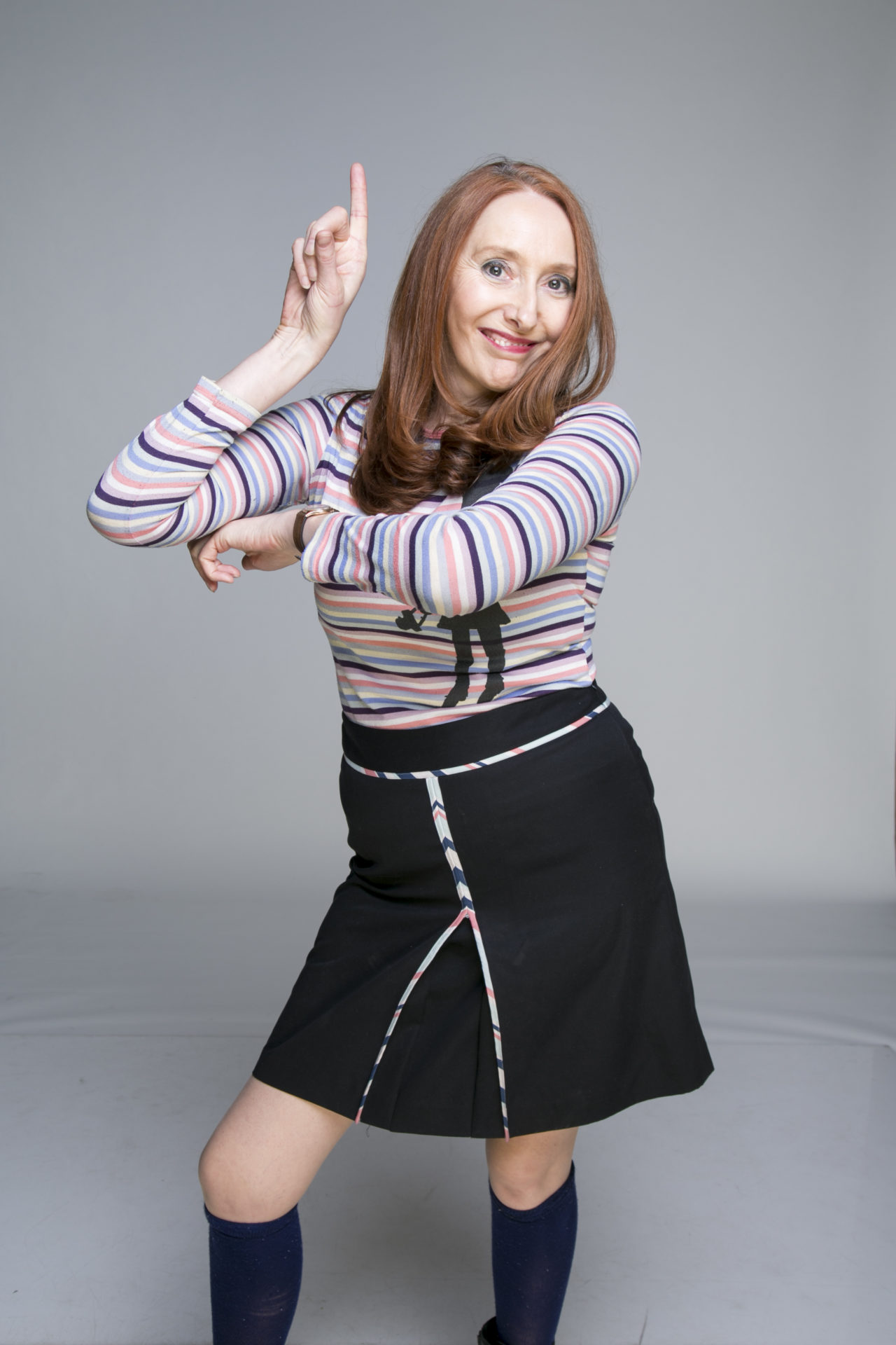 A woman with red hair striking a pose. Wearing a black skirt and a stripy shirt