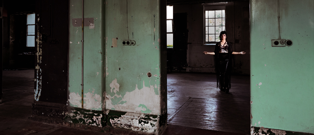 two doorways set into an old, neglected wall lead into the room of an abandoned building; in the background of one, a figure in all black can just be made out