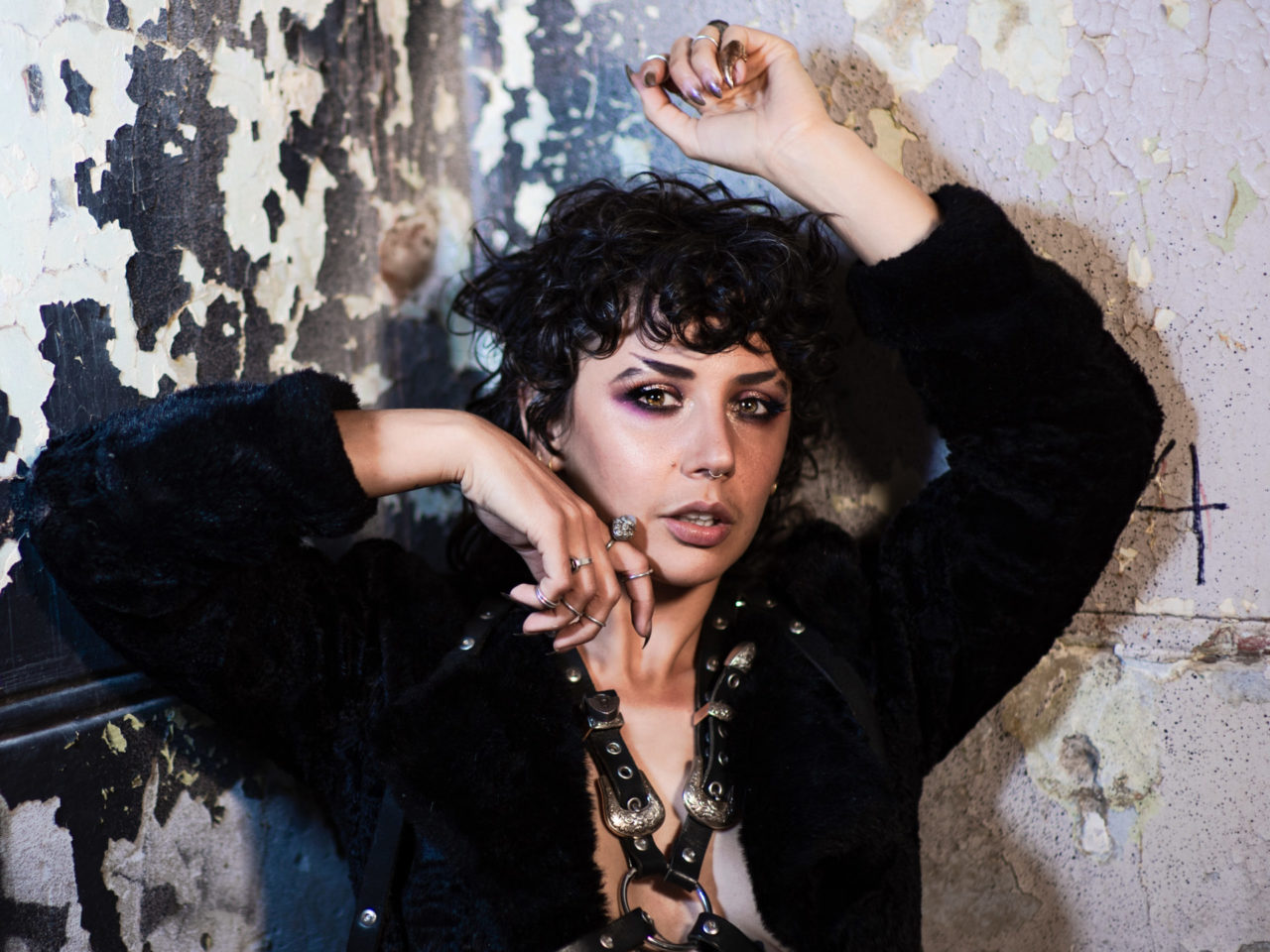 an androgynous, dark featured figure in a black fur coat and leather harness rests against a paint chipped wall with a number 4 scrawled hastily on it.