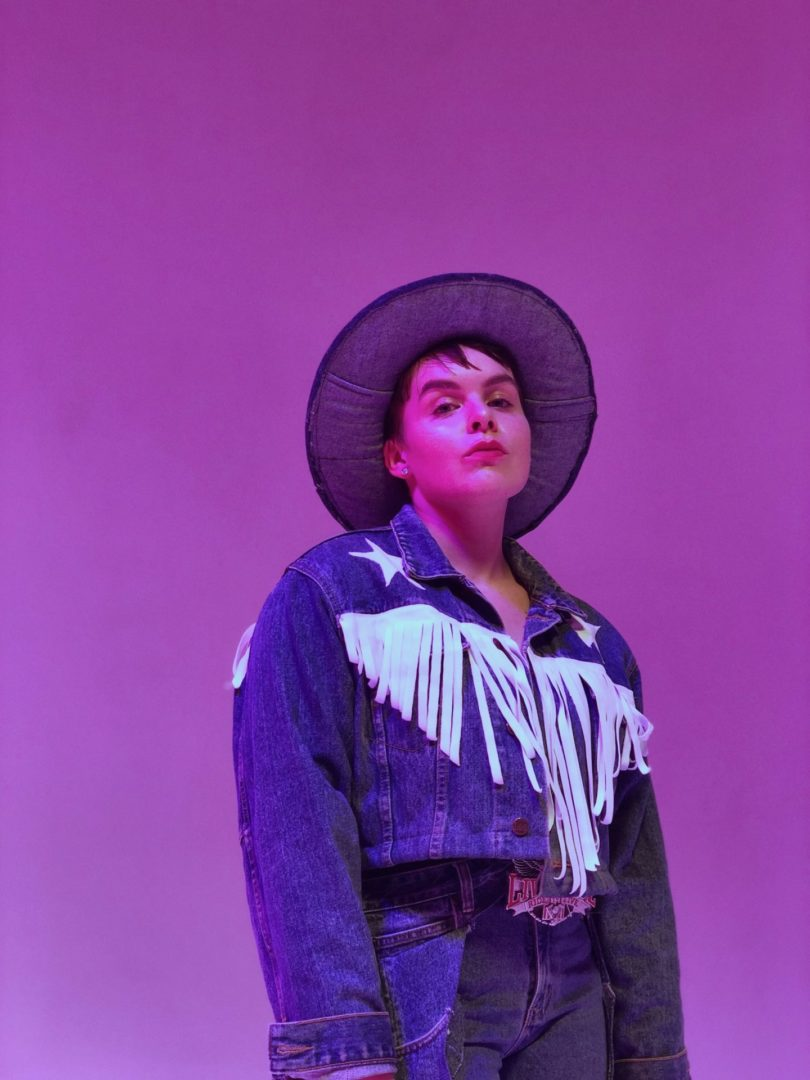 A person in a cowboy outfit posing on a purple background