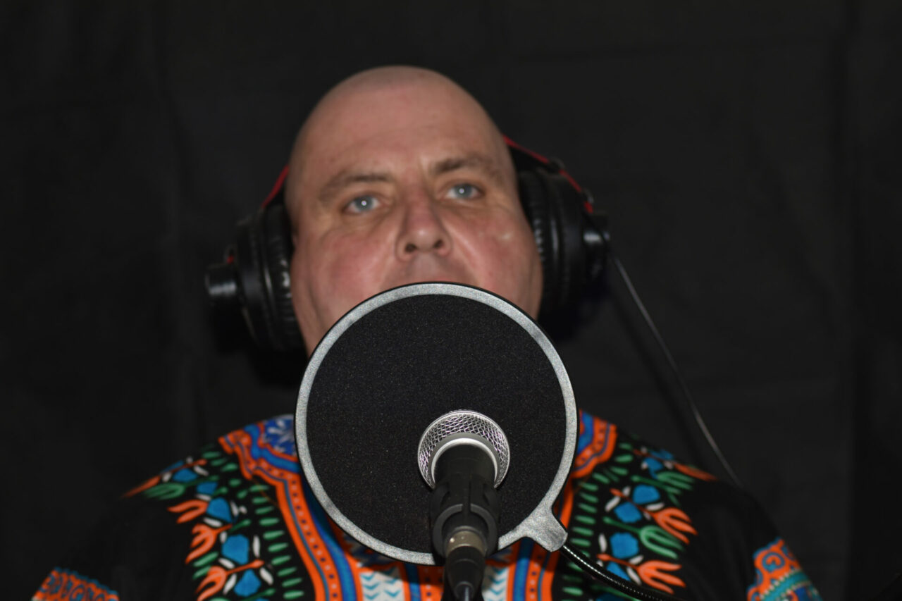 Raphael has sparkling dancing blue eyes and a shaved head. He is wearing headphones speaking into a microphone recording an interview.