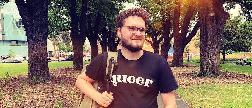 """Sam Martin, a young caucasian man wearing black tee shirt with """"queer"""" in white letters and a clear hearing aid, walks through a park"""