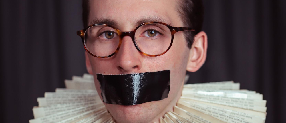 A closeup of a despondent man looking towards the camera, wearing round-framed glasses, a combover, black tape over his mouth, and an Elizabethan-inspired ruff around his neck, made out of recycled book pages.