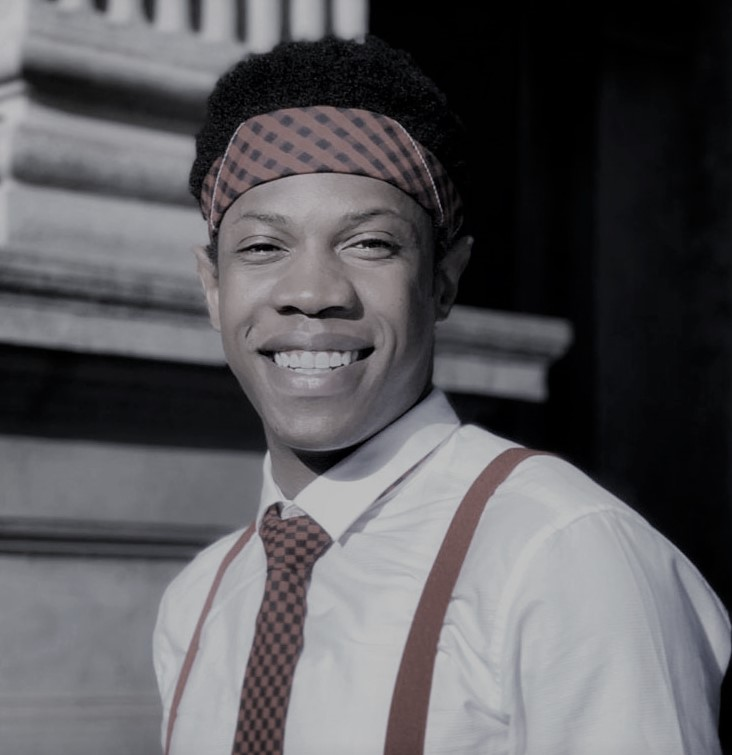 A black man with a broad welcoming smile. He wears a shirt with a tie and suspenders with a head scarf around his forehead.