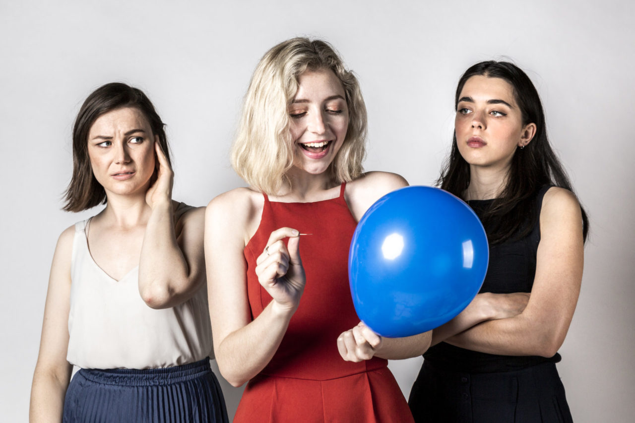 Three women in front of a white photo backdrop. The woman on the left has brown hair and wears a white blouse. She holds her hand up to her ear as she looks with a worried expression at the woman in the middle. The woman in the middle has blonde hair and is dressed in red. She has a big smile on her face, looking at a blue party balloon she is holding which she is about to burst with a pin. The woman on the right has dark hair and wears a black pantsuit with her arms crossed in front of her. She stares challengingly at the woman in the middle.