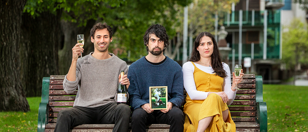 Carl holds a photo of his dog Grover. Peter looks cheerful with a bottle of champagne and a glass. Sonia looks annoyed, holding a glass.
