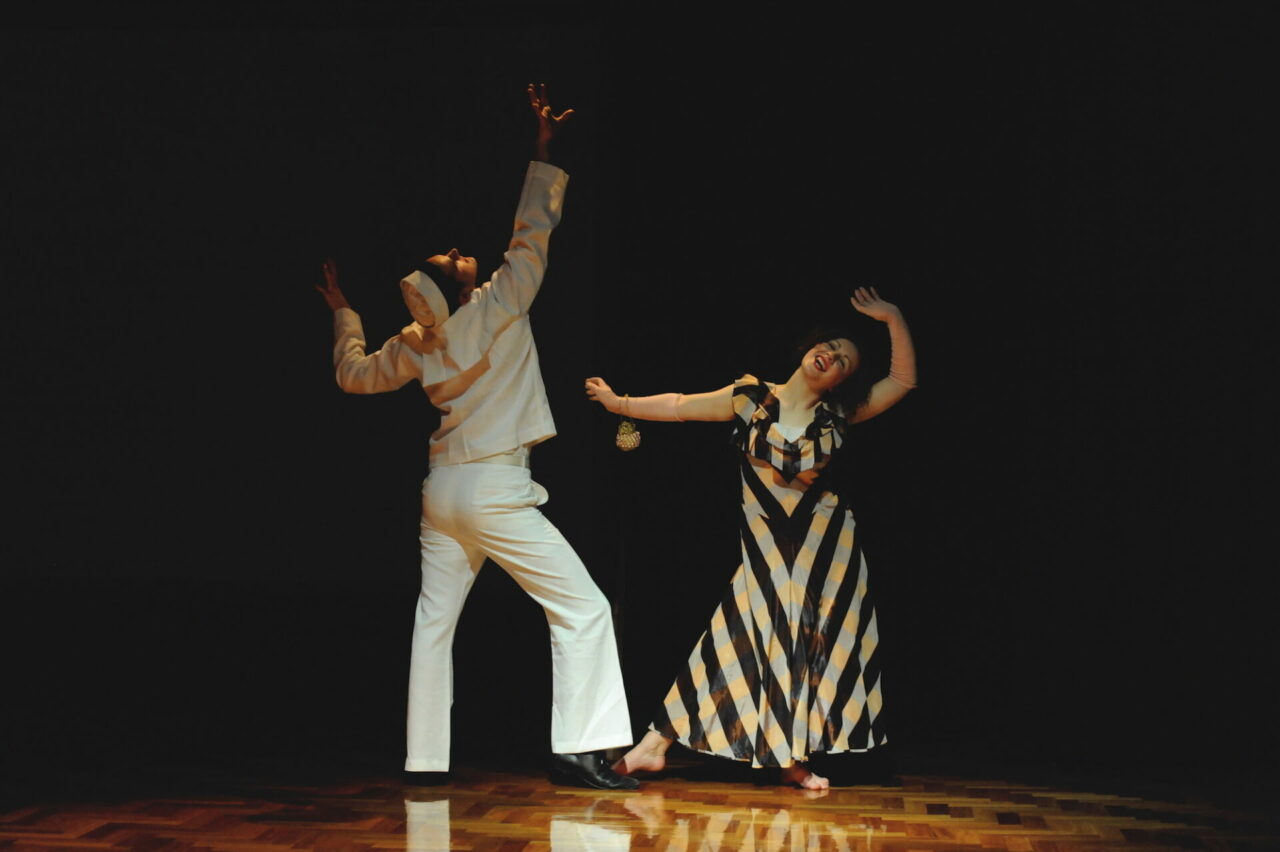 A young woman and an American sailor dance the Jitterbug.