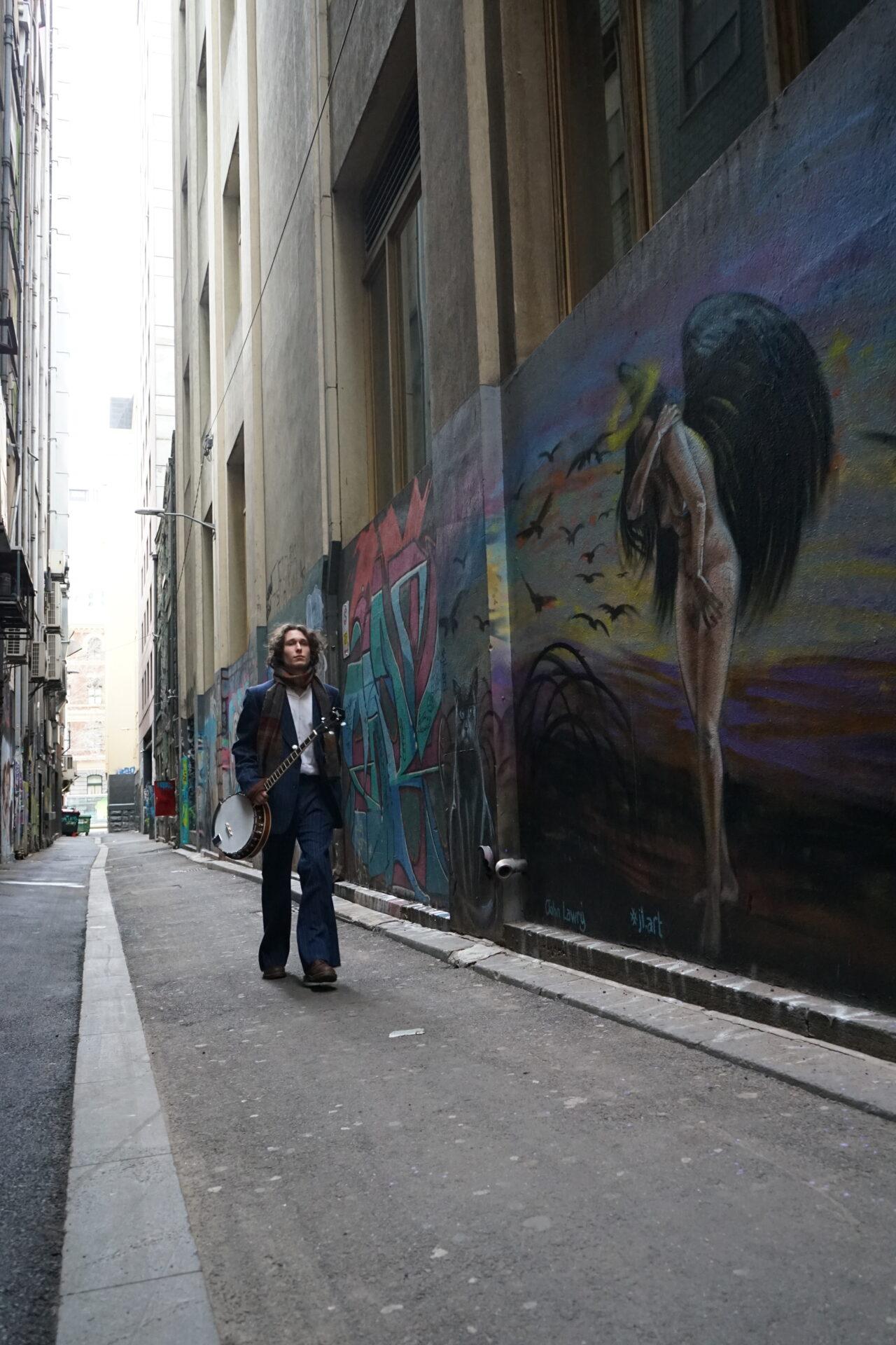 A man walking in a graffitied lane way.