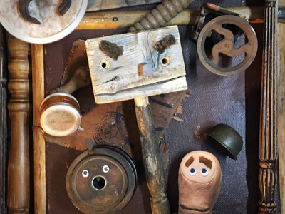Amongst some salvaged wood, a trio of wooden puppet characters look nervously at each other.