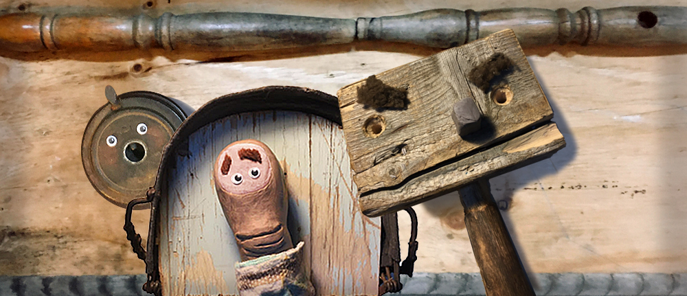 Amongst some salvaged wood, a trio of wooden puppet characters look nervously at each other