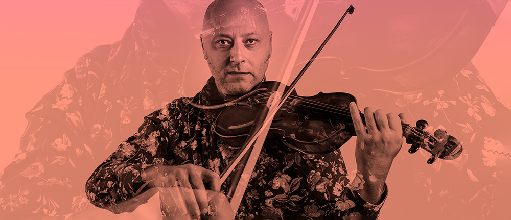 A man in a floral shirt plays violin, looking intensely into the camera.