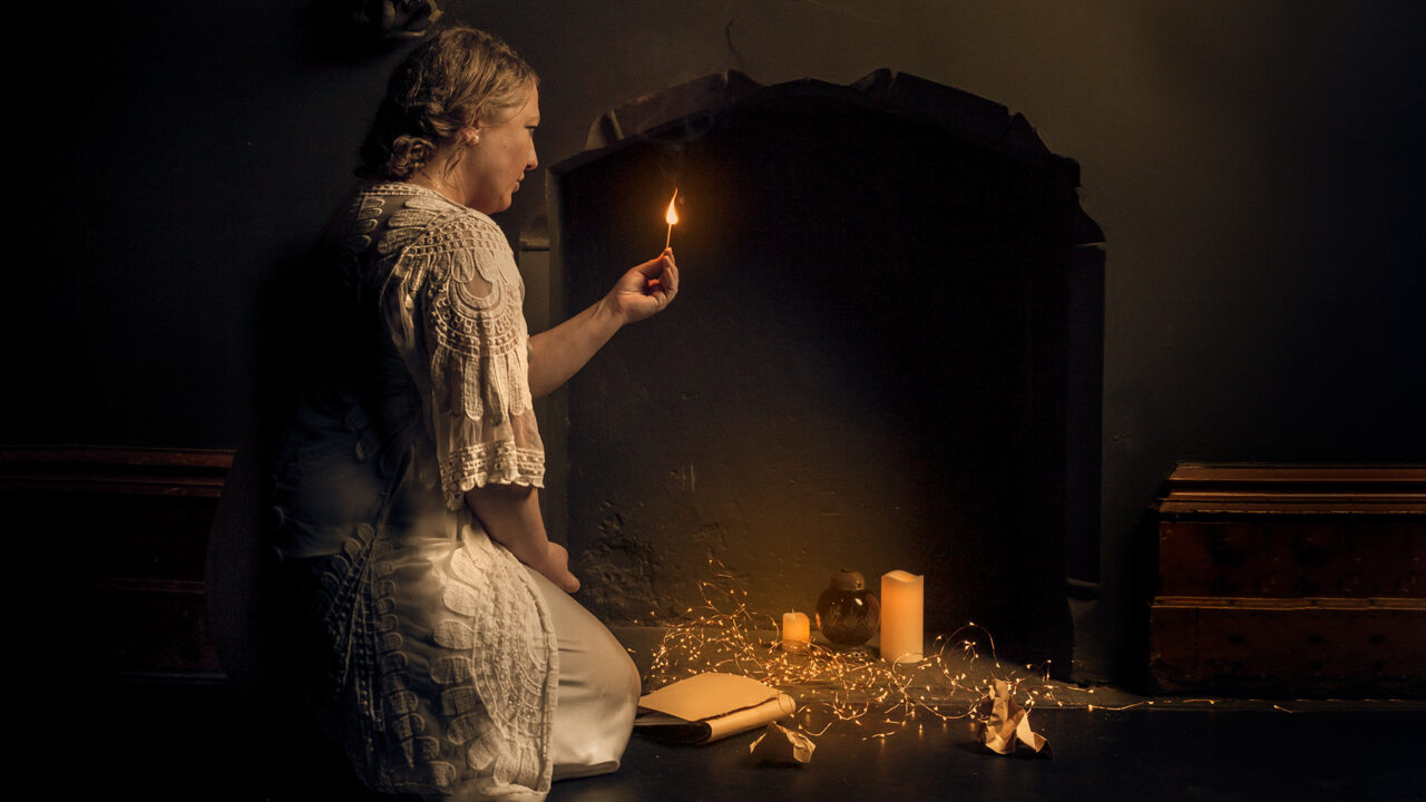 An outline of a female lighting a match next to a fire place.