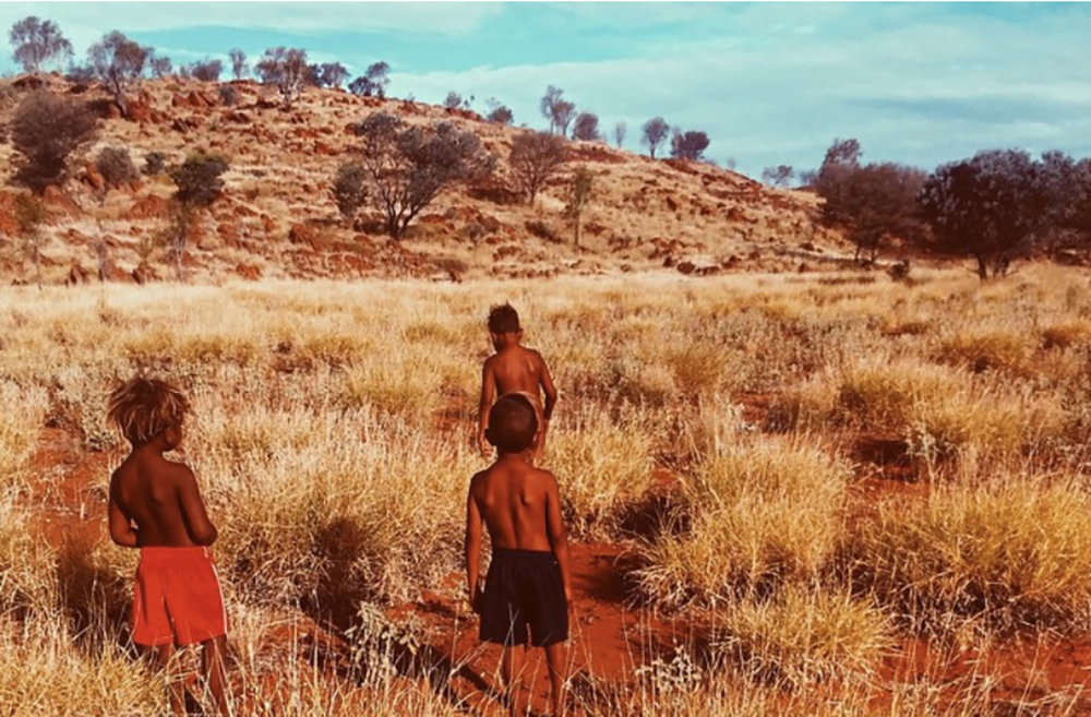 A desert landscape with three young Indigenous children walking towards a mountain through dry grasslands.