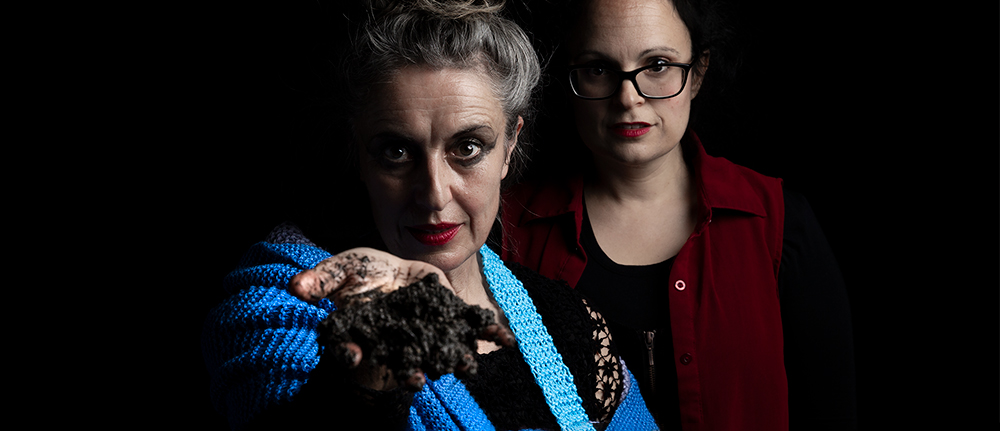 Two women, side by side, looking directly at the viewer. One woman has a coil of knitting in blues, greens, grey curled around her shoulder and wrist, she offers a handful of mud to the viewer.
