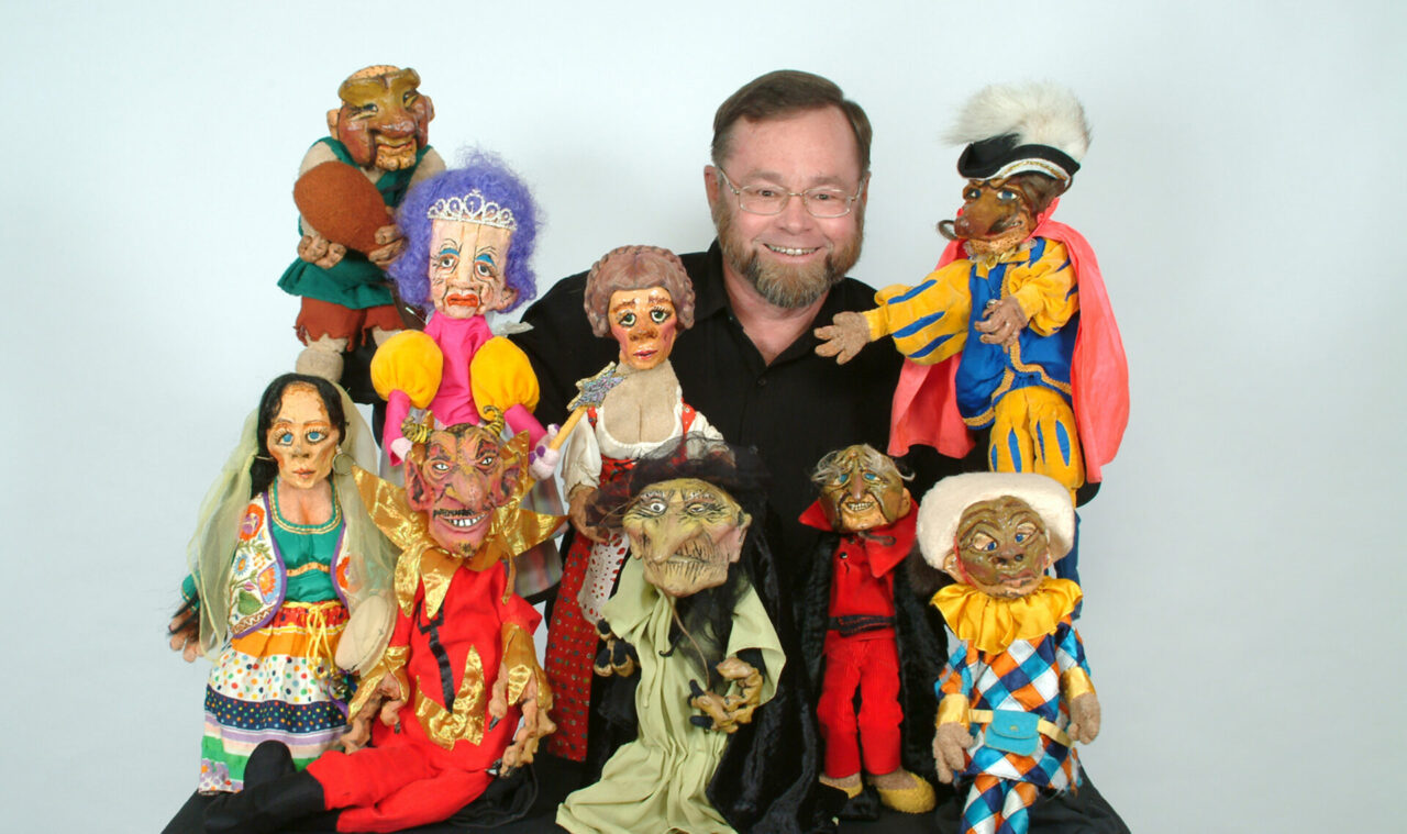 A picture of a man surrounded by puppets