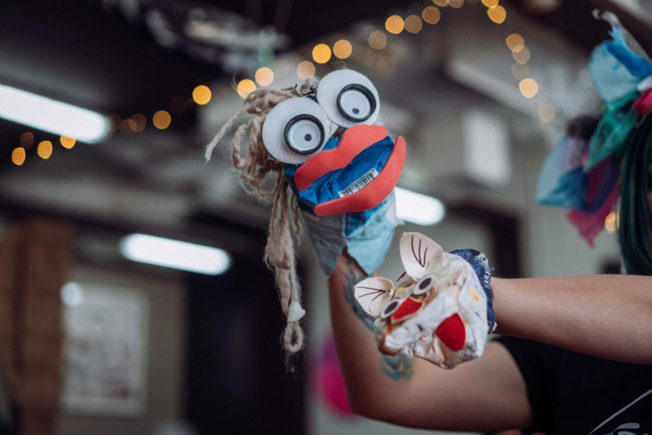 A hand held puppet with a cute face made out of rubbish