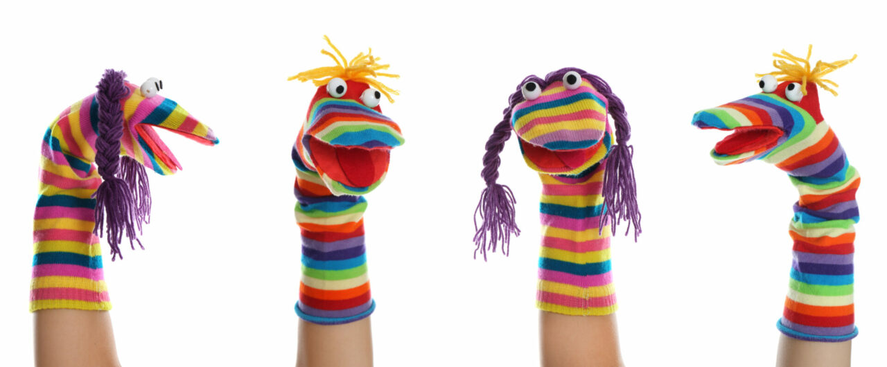 Four rainbow sock puppets looking in different directions.
