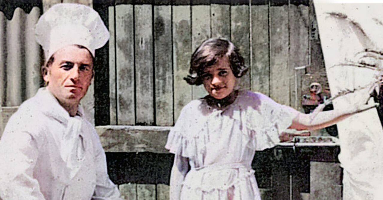 A young girl of 10 years old stands next to a sitting man who is her family's restaurant's chef, in front of an old wooden suburban fence with the chimneys of East Melbourne behind her.