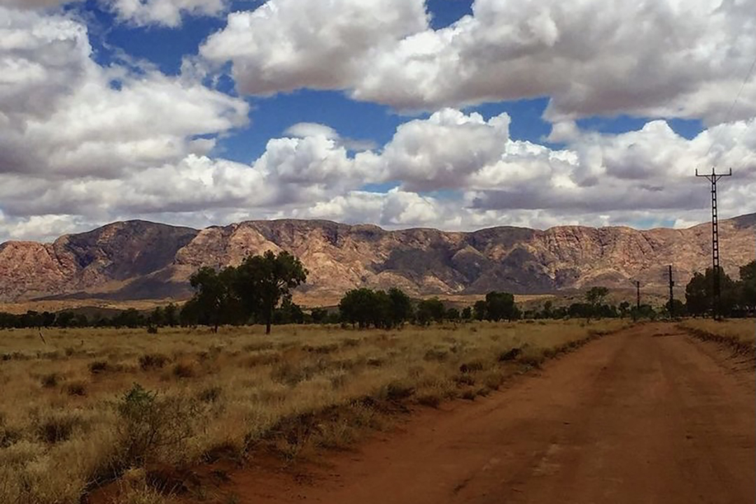 A red dirt road, a mountain and blue sky with clouds