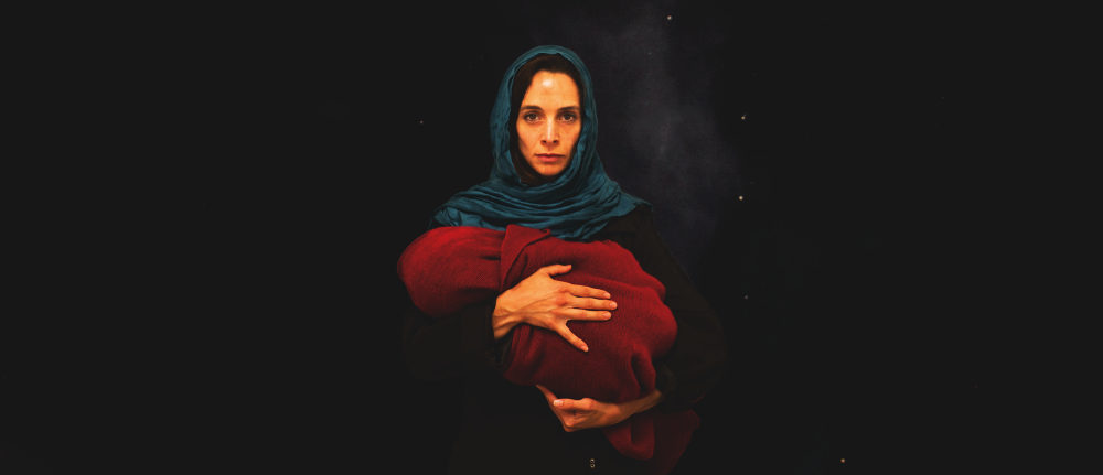 A woman in a blue scarf holds a baby wrapped in a red blanket, a dark night sky behind them.