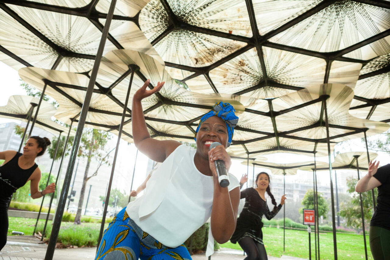 A woman with dark skin smiles and dances with participants behind her as she instructs them.